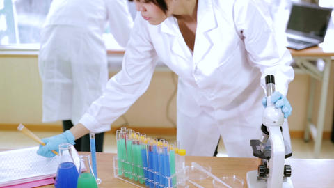 Female scientist looks into microscope takes notes Footage