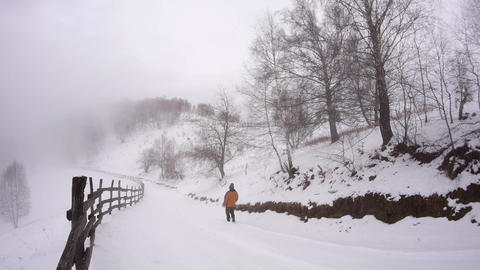 Tourist dressed in orange down on a snowy road in the forest 760c Footage