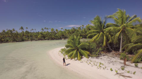 Aerial View Of A Girl Walking In A Tropical Lagoon With White Beach And Palm Tre stock footage