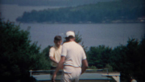 1969: Dad teaching son table tennis at scenic outdoor location Footage