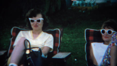 1969: Women lounging in 60's style white framed sunglasses on chaise chairs Footage