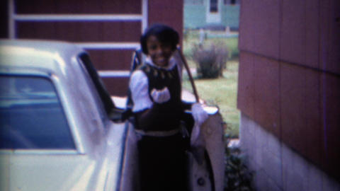 1967: African American girl blows kiss to camera as she enters car Footage