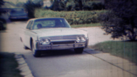 1967: White early 60's Lincoln car pulling out of driveway Footage