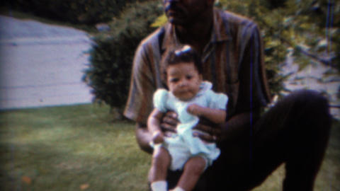 1967: African American man holding sleepy curly hair baby Live Action