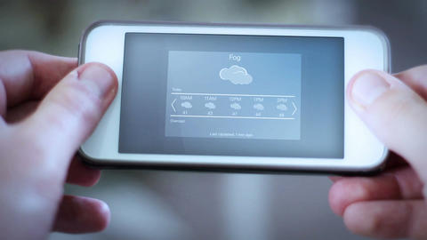 Man looks down at smartphone app with a weather app interface - Foggy day Live Action