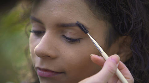 Makeup artist preparing beautiful young female for shoot, enhancing eyebrows Footage