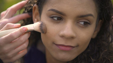 Pretty face of beautiful smiling female actress, make-up artist applying powder Footage
