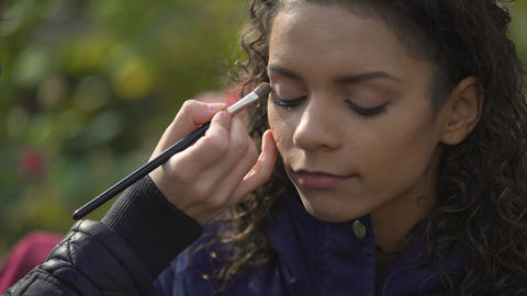 Makeup artist applying eyeshadow on eyes of model or actress, beauty blog Footage