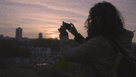 Happy female student shooting video of beautiful sunset in big city on gadget Live Action