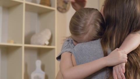 Woman comforting her upset or sick child carefully, mother hugging sad daughter Footage