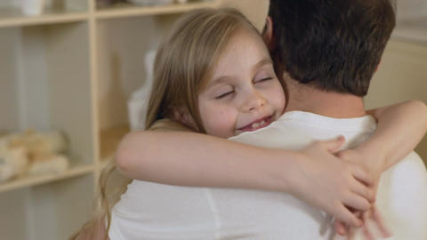 Beautiful little girl hugging father gently with happy smile on face, family Footage