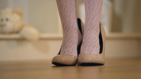 Little girl walking in adult women's elegant high heel shoes, childhood memories Footage