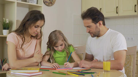 Girl drawing pictures, looking at parents with love, enjoying leisure together Footage