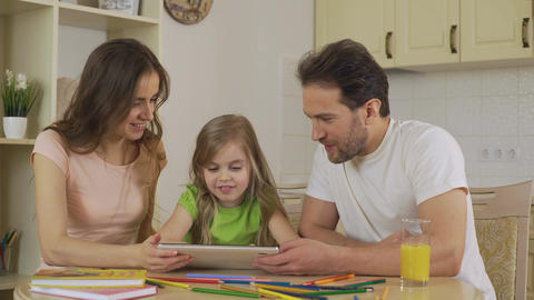 Parents showing daughter application on tablet, excited girl showing thumbs-up Footage