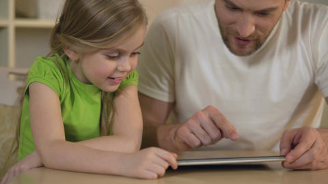 Happy father and daughter enjoying funny educational application on tablet pc Footage