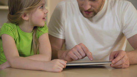 Loving father showing daughter how to use interesting mobile app on tablet Footage