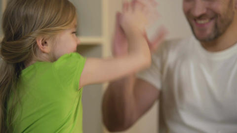 Cheerful daughter giving high five to smiling father, celebrating achievement Footage