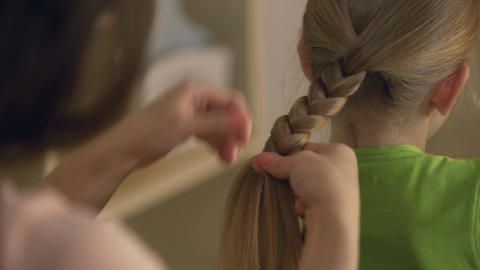 Big sister or babysitter braiding little girl's hair, woman taking care of child Live Action