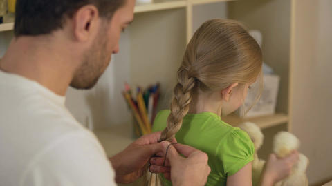 Responsible good father braiding little daughter's hair, preparations for school Footage