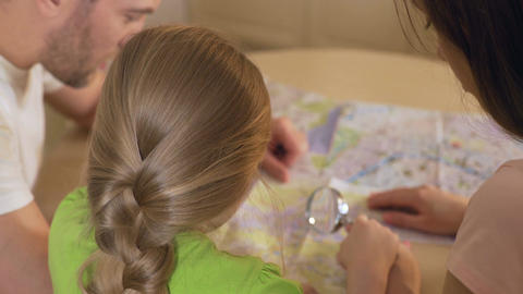 Parents and daughter looking at map, planning destination for summer vacation Live Action