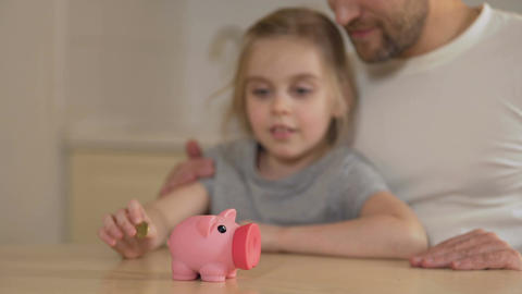 Father teaching little daughter to save money in piggy bank, giving high five Footage