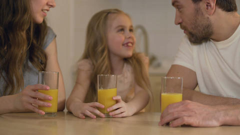 Happy healthy family drinking orange juice with smiles on faces, morning at home Footage