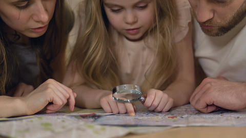 Parents learning geography with daughter, studying map through magnifying glass Footage