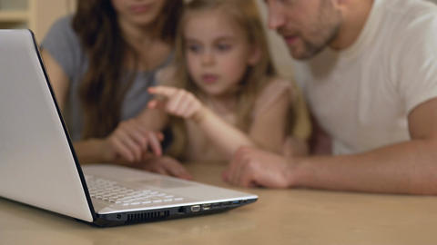 Family using laptop for shopping, booking tickets online or viewing pictures Footage