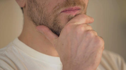 Close-up of serious young man with beard rubbing chin, having doubts, thinking Footage