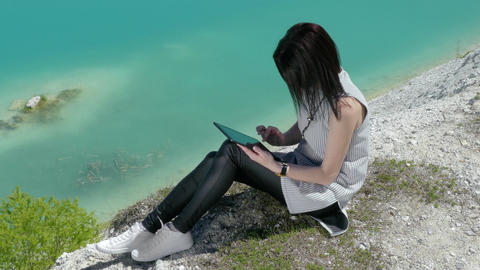 Young Woman Use A Tablet Sitting On A Hill Near Beautiful Lake Footage