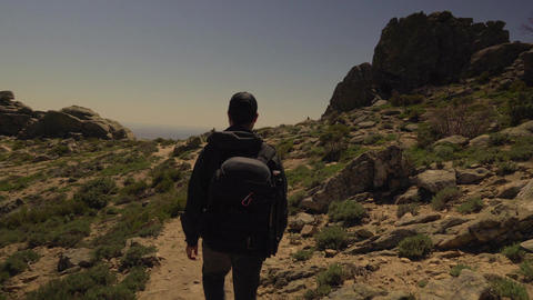 Track shot of young man hiking in the mountains Footage