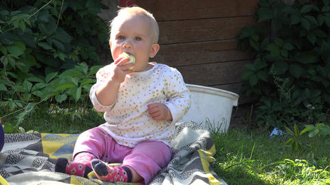 Adorable baby child eating apple fruit in rural garden. 4K Footage