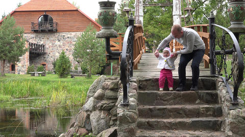 farther baby daughter spend freetime on stone bridge in park. 4K Footage