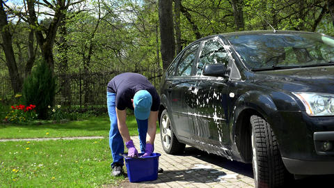Young man washing his black car with soapy sponge Footage