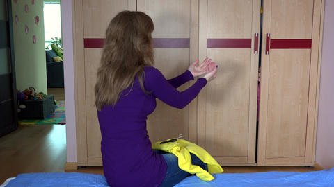 Mother asking her adorable daughter girl hiding in closet to put on dress Footage