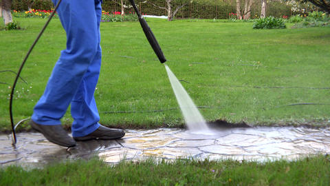 Man walk and wash path with water pressure tool in garden Footage