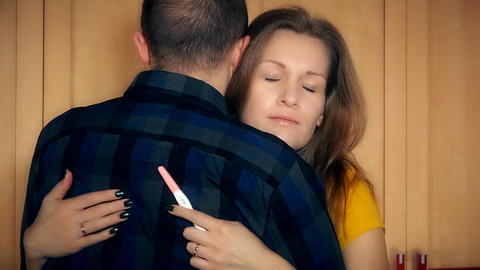 Worried woman with positive pregnancy test hug her man and think Footage
