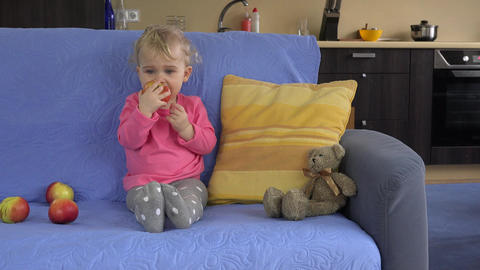 Gorgeous toddler kid child sitting on the sofa and eating big apple fruit Footage