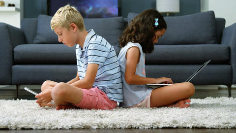 Siblings sitting back to back and using digital tablet, laptop in living room Live Action