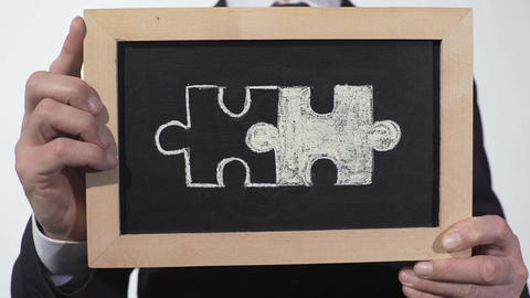Connected puzzles drawn on blackboard in businessman hands, partnership symbol Footage