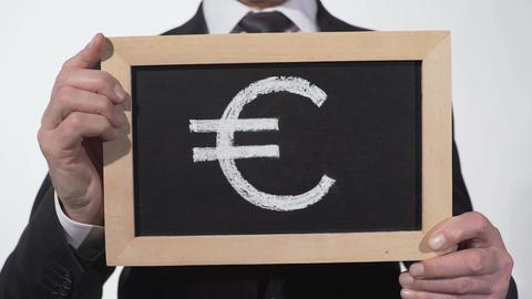 Euro symbol drawn on blackboard in businessman hands, European currency, finance Footage