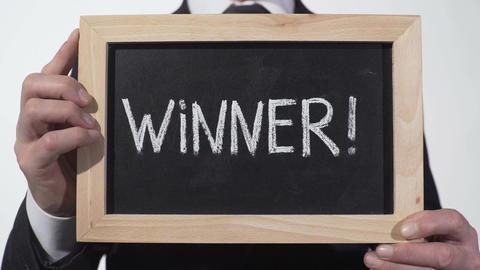 Winner exclamation written on blackboard in businessman hands, successful person Footage
