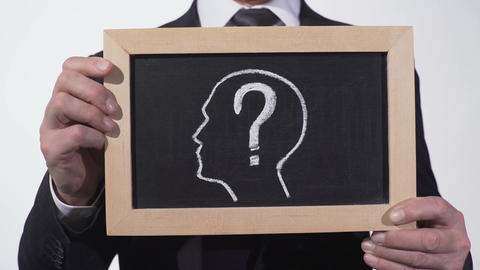 Questionmark head image on blackboard in businessman hands, searching solution Live Action