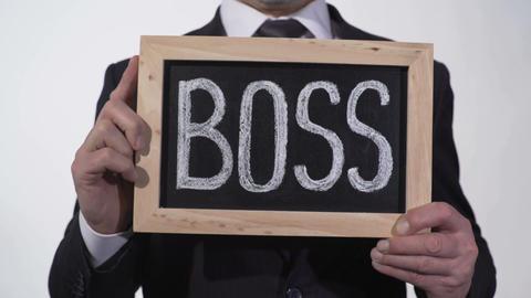 Boss written on blackboard in businessman hands, corporation top manager, leader Footage