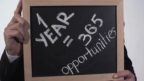 One year is 365 opportunities motivation on blackboard in businessman hands Footage