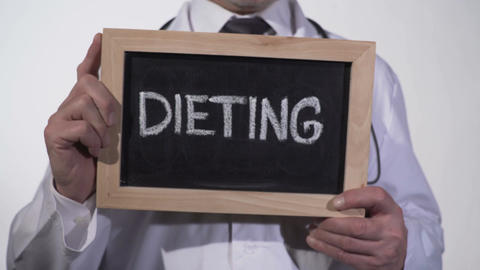Dieting written on blackboard in doctor hands, nutritionist recommendations Footage