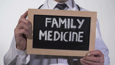 Family medicine text on blackboard in physician hands, comprehensive healthcare Live Action