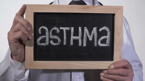 Asthma written on blackboard in doctor hands, genetic lung disease, bad ecology Footage