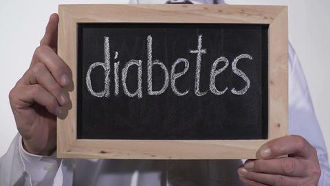Diabetes written on blackboard in therapist hands, high blood sugar problem Footage