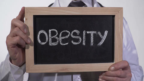 Obesity written on blackboard in doctor hands, healthy nutrition recommendations Footage